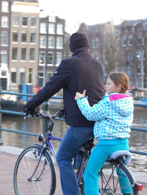 Daughter sitting on the back carrier of her father's bike in Amsterdam