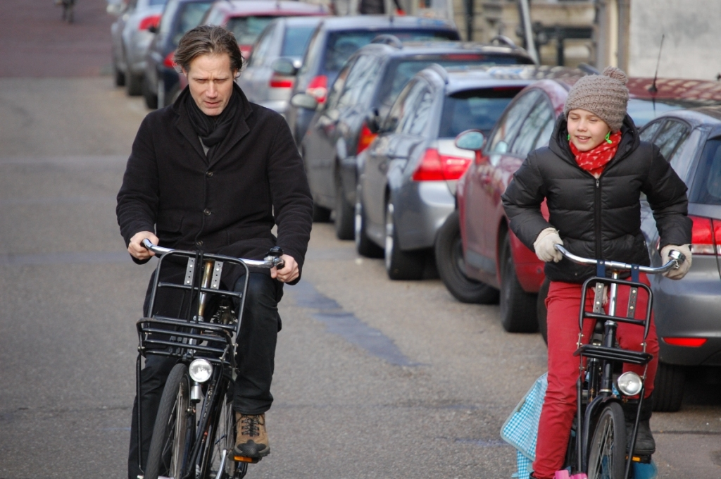 Father and daughter chatting while cycling in Amsterdam