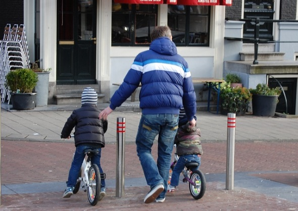 Father and sons on bikes by Joni
