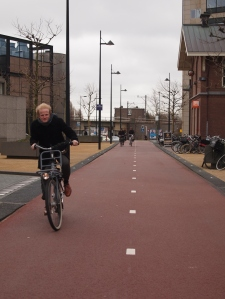 Eske cycling on a windy day in Amsterdam
