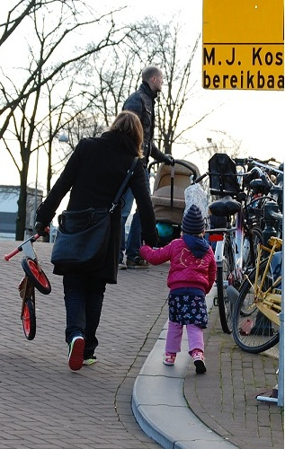 Mother carrying bicycle by Joni
