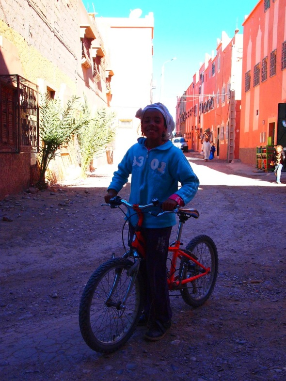 Girl in Ouarzazate showing her red bicycle